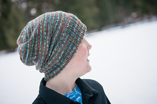 A person outside in the winter looking slightly away from the camera and wearing a variegated slouch knit hat with a wide ribbed brim folded up.