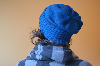 View of a woman's back wearing a striped blue scarf and a bright blue slouchy knit hat with the ribbed brim folded up and some curls sticking out.