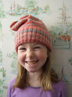 Blonde girl, about 6 years old, wearing a pink slouchy knit hat with the ribbed brim folded up with vintage wallpaper in the background.