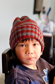 A boy, about five years old, looking at the camera with a neutral expression and wearing a red and grey striped knit hat with a wide ribbed brim folded up.