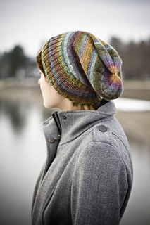 Woman with short hair wearing a striped multi-coloured slouchy knit hat with the ribbed brim folded up and a lake in the backgronud.