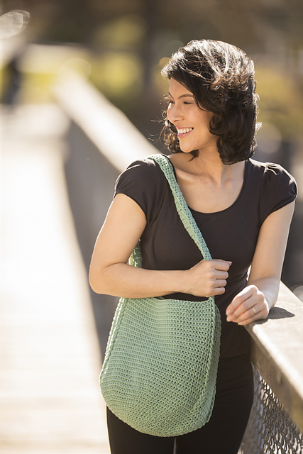 A slim woman with a golden skin one and shoulder length dark hair, wearing a dark brown cap sleeve fitted tshirt and dark trousers. She's leaning on the rail of a bridge with a blurred background. She's holding a large crocheted bag in a soft light green. The bag is worn covering her entire abdomen.