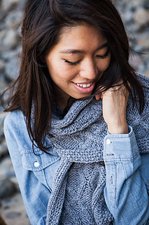 [Image Description: A woman wearing a bulky-weight cable knit scarf around her neck. One end of the scarf is falling in front of her chest.]