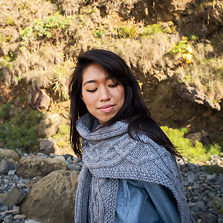 [Image Description: A woman wearing a bulky-weight cable knit scarf around her neck and shoulders. The scarf is spread over her shoulder, and a knotted cable pattern is visible.]
