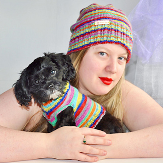 A woman with blonde hair and ruby lipstick wearing a striped hat with her arms around a little black adorable dog who is wearing a matching striped sweater.