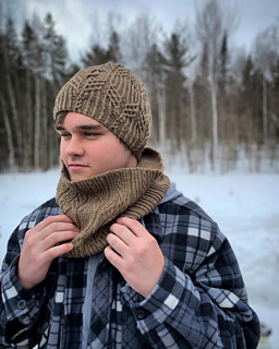 young man wearing a matching knitted cowl and hat set, a blurred winter scene in the background.  He is adjusting the cowl with his hands.