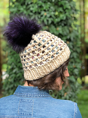 A girl with brown hair and a jean shirt, facing away from the camera and looking over her shoulder, wearing a cream hat with a purple pompom.