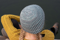 A young girl wearing a two-colour blue brioche folded brim hat, viewed from above, and a yellow hand-knit sweater, sitting on a dock and looking over a lake.