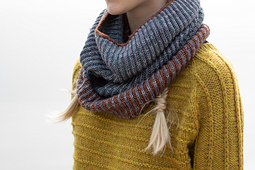A young girl wearing a yellow hand-knit sweater and a grey, blue, and orange brioche cowl.