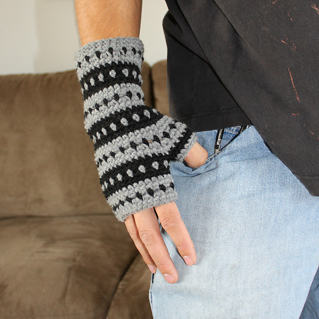 close up of a man's hand with thumb in pocket. He has on a striped fingerless glove