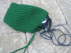 [Image Description: A small green bag done in 1 by 1 ribbing, with a twisted cord drawstring and a pair of headphones partially out.]