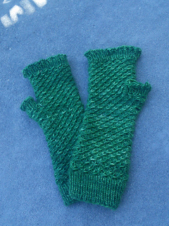 [Image Description: A pair of fingerless mittens laying flat and slightly overlapping, with a spiralling textured pattern on the cuff and hand.]