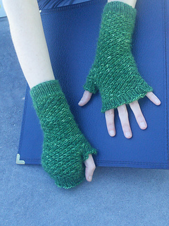 [Image Description: Someone wearing a pair of fingerless mittens. The mittens are knit in a dark green fingering-yarn and use a textured star stitch over the body of the mitten.]