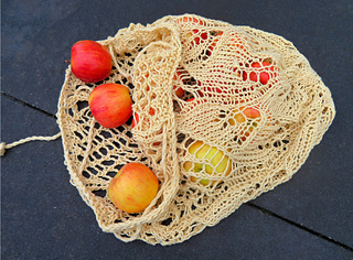 [Image Description: An open mesh bag laying flat. The drawstring is open and the apples inside are just starting to roll out.]
