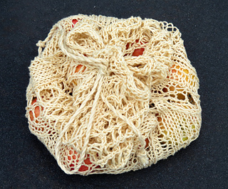 [Image Description: A cream-coloured mesh bag with a drawstring. The drawstring is pulled closed and has been tied into a bow.]