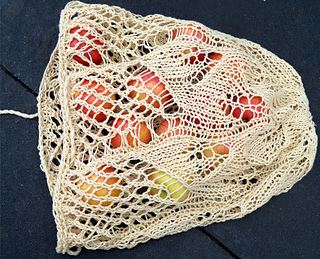 [Image Description: An open mesh bag laying on its side. The base of the bag is lace knit in a leaf pattern, which transitions to an open mesh.]