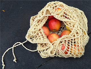 [Image Description: A drawstring bag mesh bag left partially open. The bag has apples inside.]