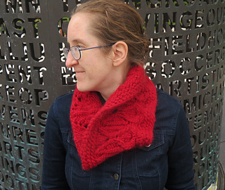 [Image Description: A woman wearing a bright red bulky-knit cowl.  The cowl has a cable and lace knit pattern.]