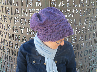 [Image Description: A woman wearing a deep purple worsted-weight knit hat. You can see the top of the hat. There is a celtic-knot cable band is going around the head just above the ribbing.  The top of the hat gathers where the stitches were pulled in. ]