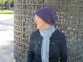 [Image Description: A woman wearing a deep purple worsted-weight knit hat. She is shown in profile. The ribbing of the hat sits a little loose on her forehead. There is a cabled band above the ribbing of the hat. The hat falls in a slouch at the back of her head.]