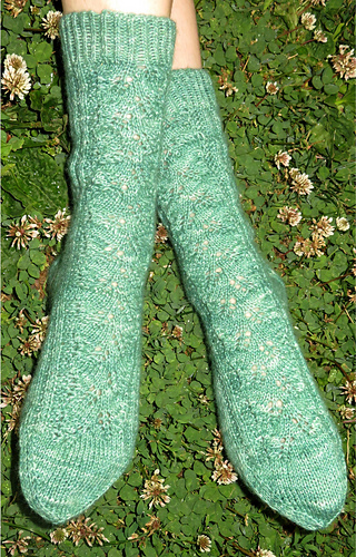 [Image Description: Someone wearing a pair of green socks.  They have a lace leaf pattern along the leg and top of the foot.]