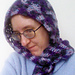 [Image Description: A woman wearing a hood with a scarf.  The hood is done in worsted-weight crochet in a chevron pattern.  The yarn is variegated yarn that runs between purple, black, and grey. ]