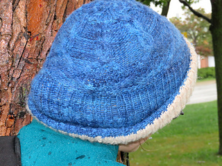 [Image Description: Someone wearing a cabled hat made in blue wool. They are facing away from the camera. The hat brim is flipped up and you can see the reverse side of the hat, knit in off-white wool.]