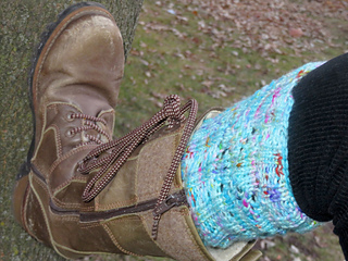 [Image Description: Someone wearing a sky blue boot topper knit in worsted yarn; with lace eyelets visible]