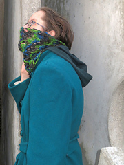 [Image Description: A woman wearing a crochet lace cowl done in a variegated yarn.  The cowl is pulled up over her mouth and nose]