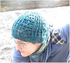 [Image Description: A woman wearing a crochet lace hat.  The hat is made in a dark teal yarn; with textured post stitches and crochet bobbles.]