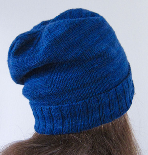 View of a brunette woman from behind with a blue slouchy knit hat.