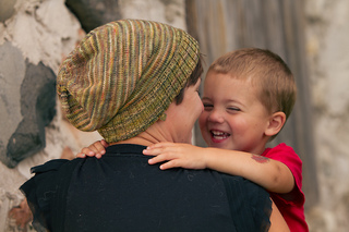 View of a woman with short hair from behind wearing a stripey knit slouch hat and holding a boy toddler who is laughing.