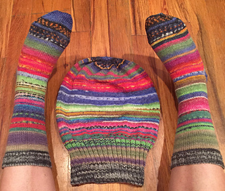 A multi-coloured Sockhead hat lying flat on a wood floor with matching socks on either side.