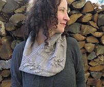 A woman with brown, curly hair looking right wearing a light grey cowl with bobble details and a stack of wood in the background.