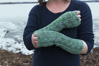 A close-up of a woman's hands wearing long fingerless gloves knit with a green speckle yarn with a wavy pattern running lengthwise down the arm and a wintery lake in the background.