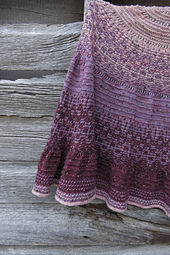 A close-up of a crescent shawl with mosaic bands in three shades of purple with a barn wall in the background.