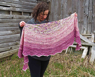 A woman holding a crescent shaped shawl in front of her knit in three shades of pink speckle yarn with a barn in the background.