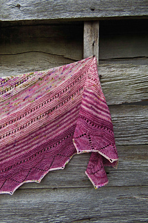 A close-up of a crescent-shaped shawl in three colours of pink speckled yarn with a barn wall in background.