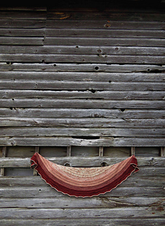 A long shot of a crescent-shaped shawl in speckled yarn and three colours (beige, peach and red) with a barn wall in background.