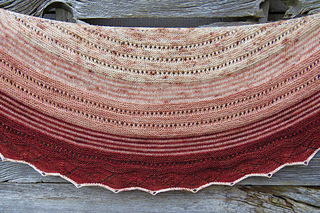 A close-up of a crescent-shaped shawl in speckled yarn and three colours (beige, peach and red) with a barn wall in background.