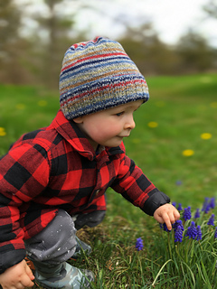 Toddler boy outside wearing a striped knit hat and wearing a red, buffalo plaid jacket.