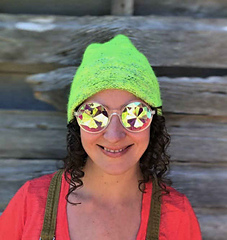 """A woman with brown, curly hair grinning and wearing a neon yellow-green hat and coloured """"hippie"""" glasses with a barn in a background."""