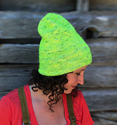 """A woman with brown, curly hair wearing a neon yellow-green hat sitting """"tall"""" with a barn in a background."""
