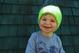 A toddler boy grinning and wearing a neon yellow-green hat with a green shingled background.