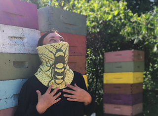 a brunette woman looking at the sky standing in front of colourful bee boxes and wearing a yellow cowl with a bee on it