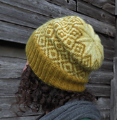 View of a woman with curly hair facing away from the camera looking at a barn and wearing a slightly slouchy mustard yellow hat with a diamond pattern.