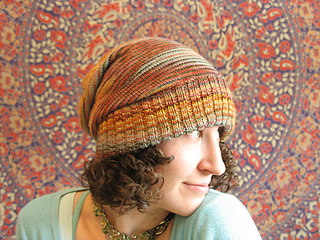 Brunette woman with curly hair wearing a multi-coloured slouchy knit hat with the ribbed brim folded up and a botanical (tapestry) background.