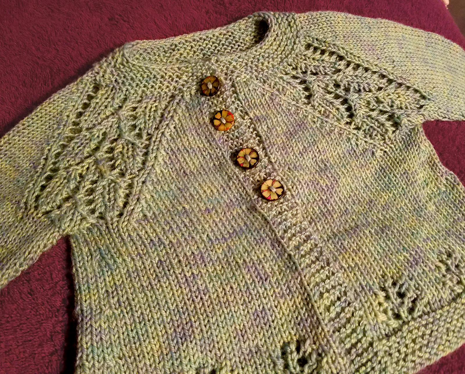 A green knit baby sweater with flower lace at the  shoulders