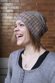 View of blonde woman with short straight hair laughing and wearing a variegated lavender knit hat with wide ribbed brim.