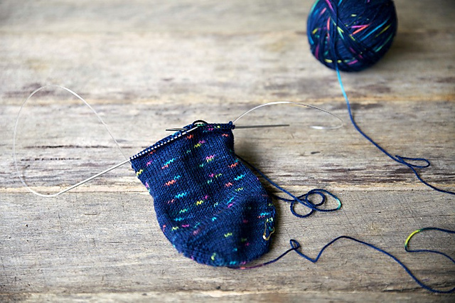 In-progress pic of knitting a sock on small circular needles, the yarn is dark navy with short dashes of bright colours (pink, blue, yellow, green, orange) that come out as short speckles and squiggles in the knitting. The project is resting on a pale wooden surface.